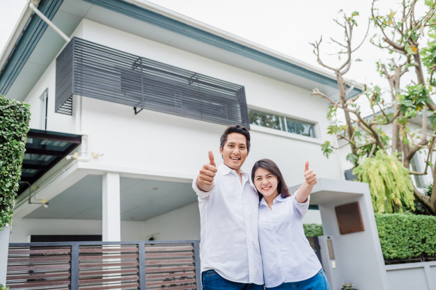 asian-couple-standing-together-in-front-of-thier-house_34840-122